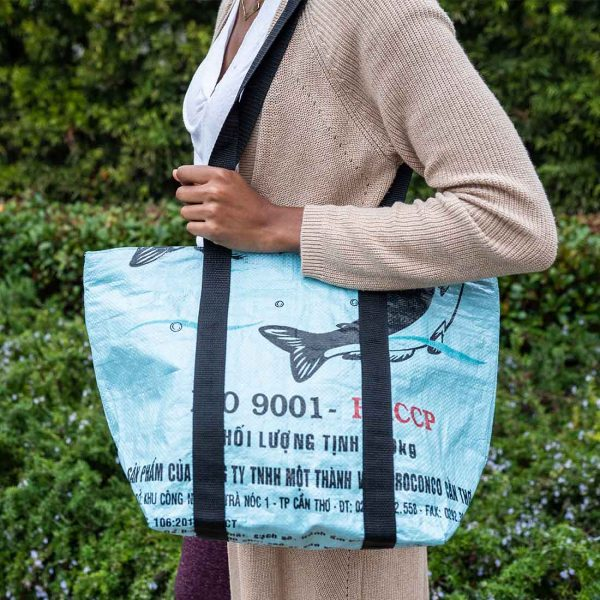 woman carrying light blue beach bag