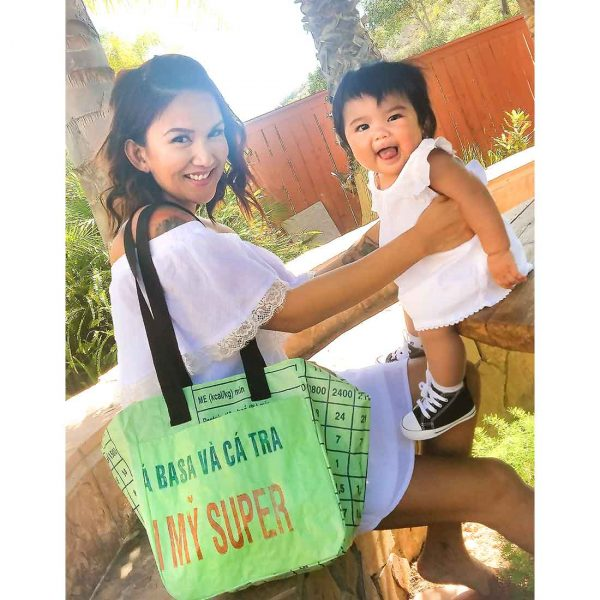 woman and baby with large green bag